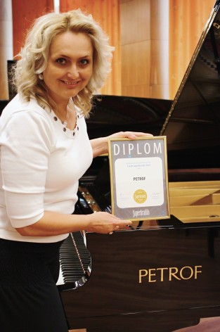 Mgr. Zuzana Ceralová Petrofová, president of the company PETROF, with the diploma of Superbrands
