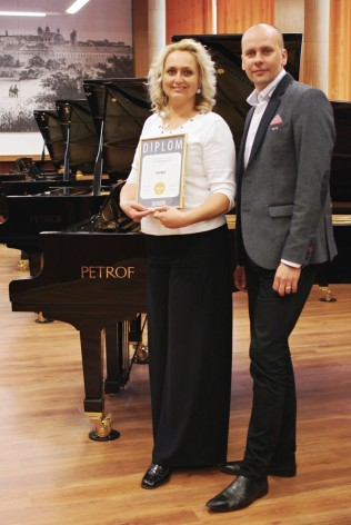 Mgr. Zuzana C. Petrofová receiving the Superbrands award for PETROF from the representative of Superbrands Czech Republic.